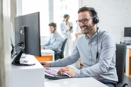 Smiling customer support operator with hands-free headset working in the office.